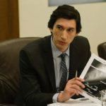 Adam Driver behind a desk